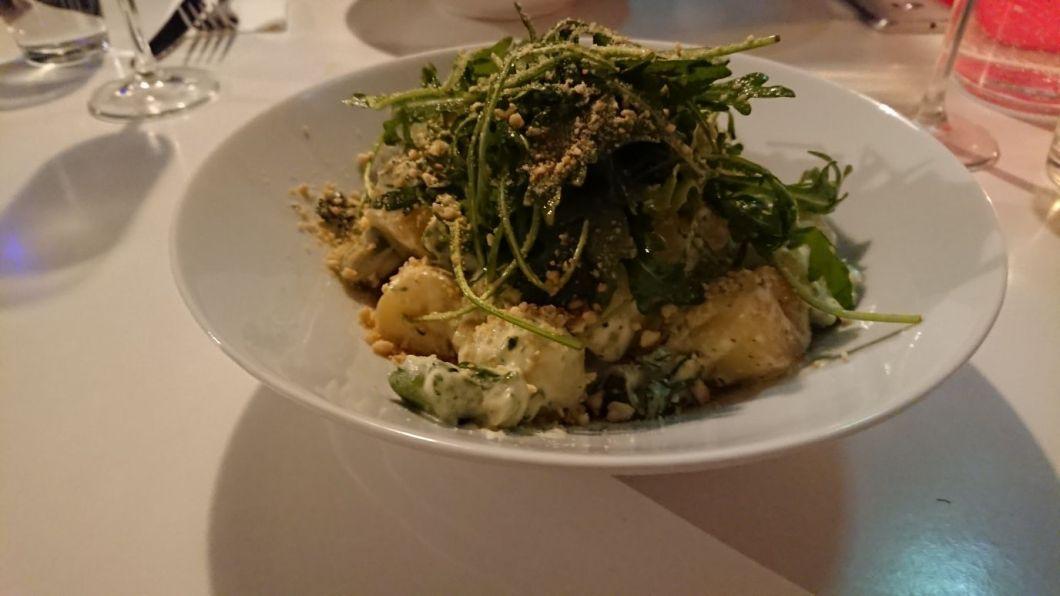 Potato gnocchi with asparagus, broccoli and pesto sauce served with rocket salad